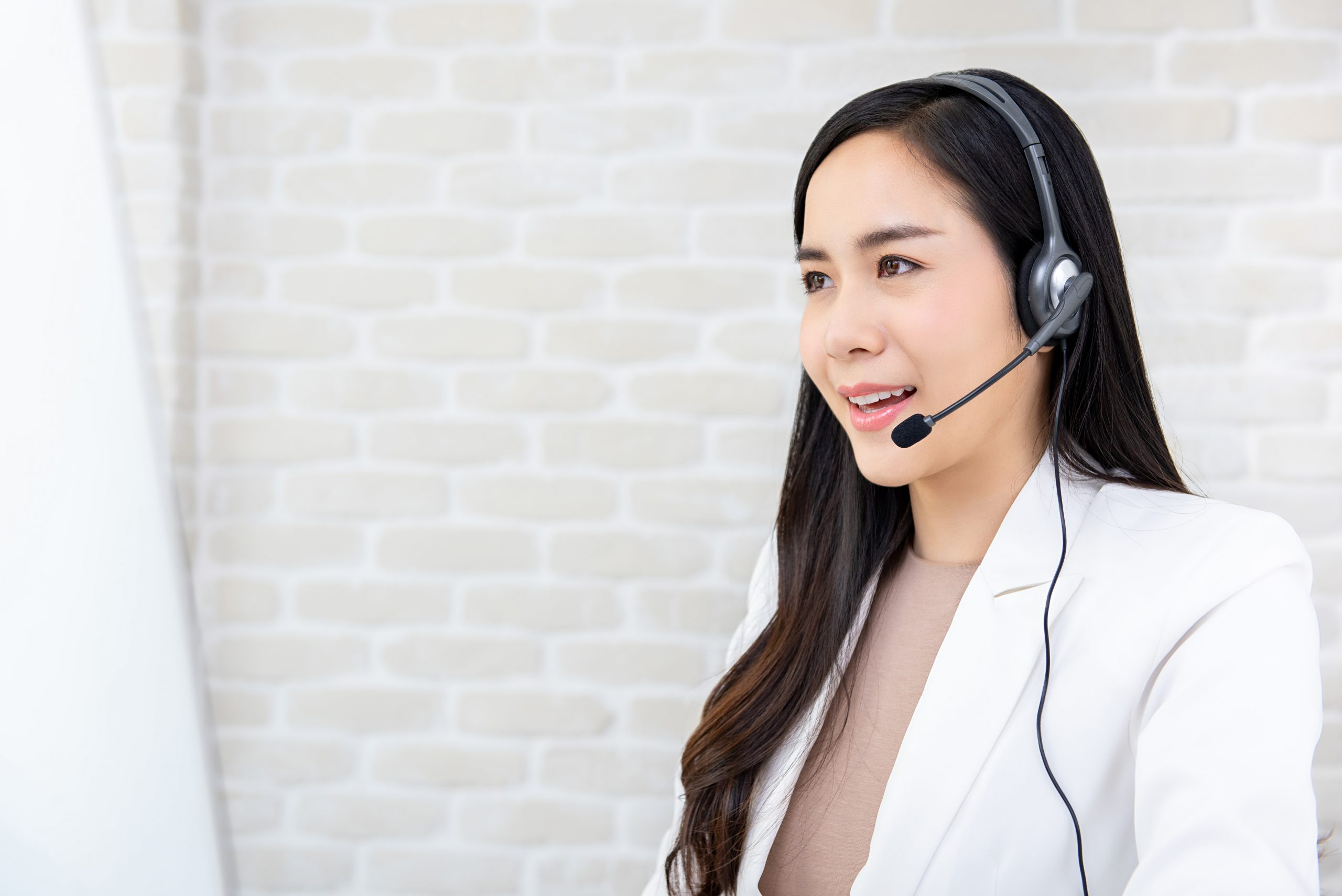 Young beautiful Asian businesswoman wearing headphone working in call center office as a customer service operator