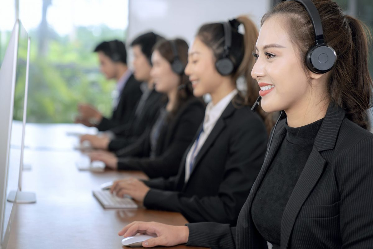 Positive Asian Female Customer Services Agent With Headset Working In A Call Center company